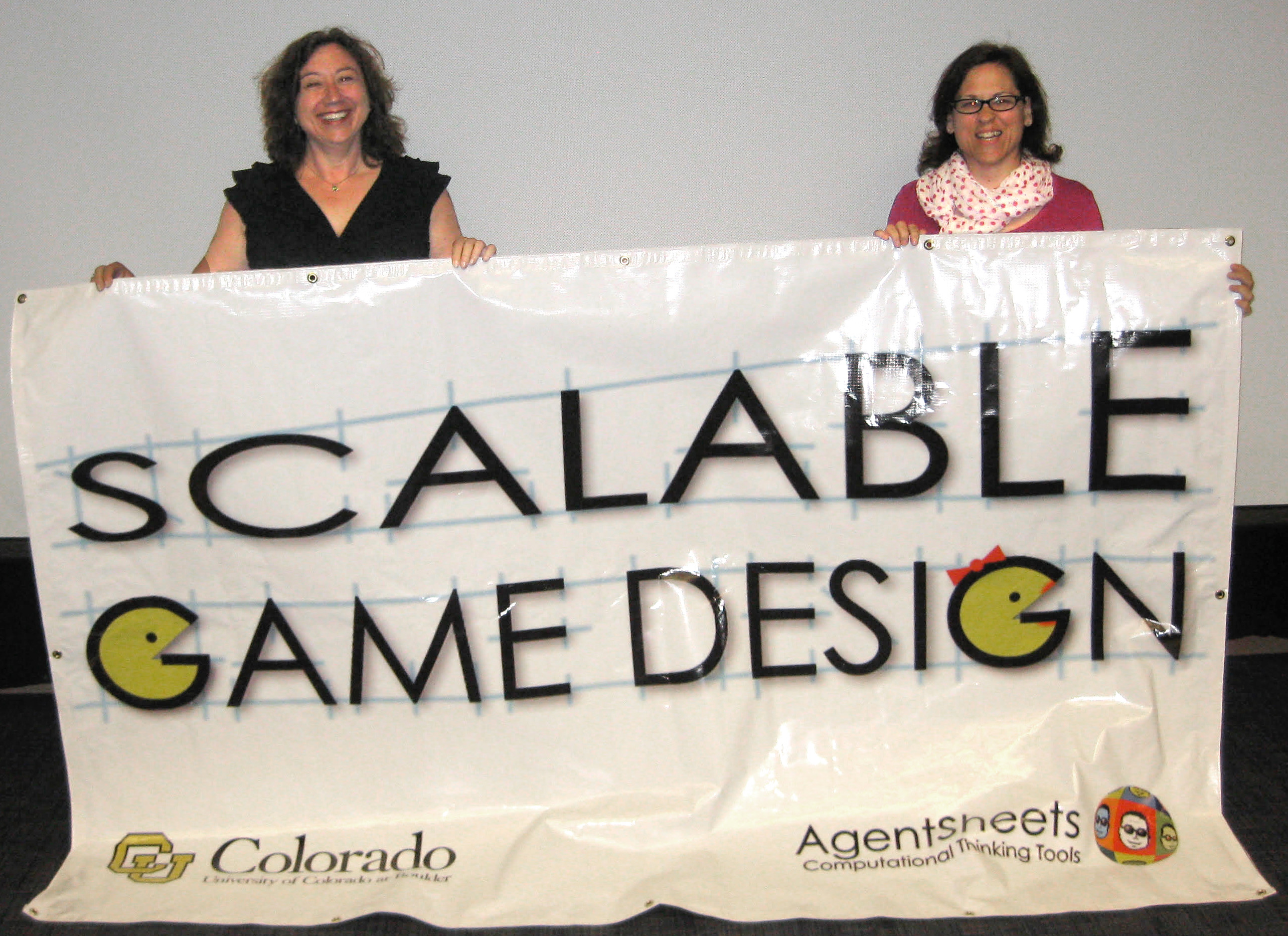Two founder of Scalable Game Design holding a Scalable Game Design sign.